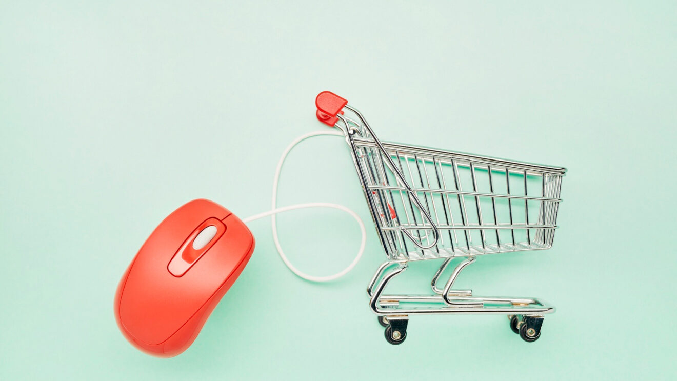 Still life of a small shopping cart and red computer mouse on turquoise background