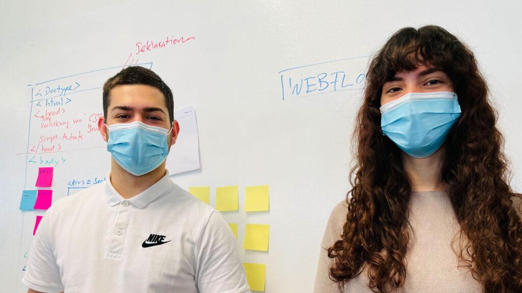 Das Bild zeigt David und Iris mit Maske vor unserem Whiteboard.
